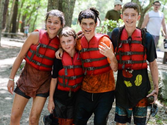 Muddy kids in life vests