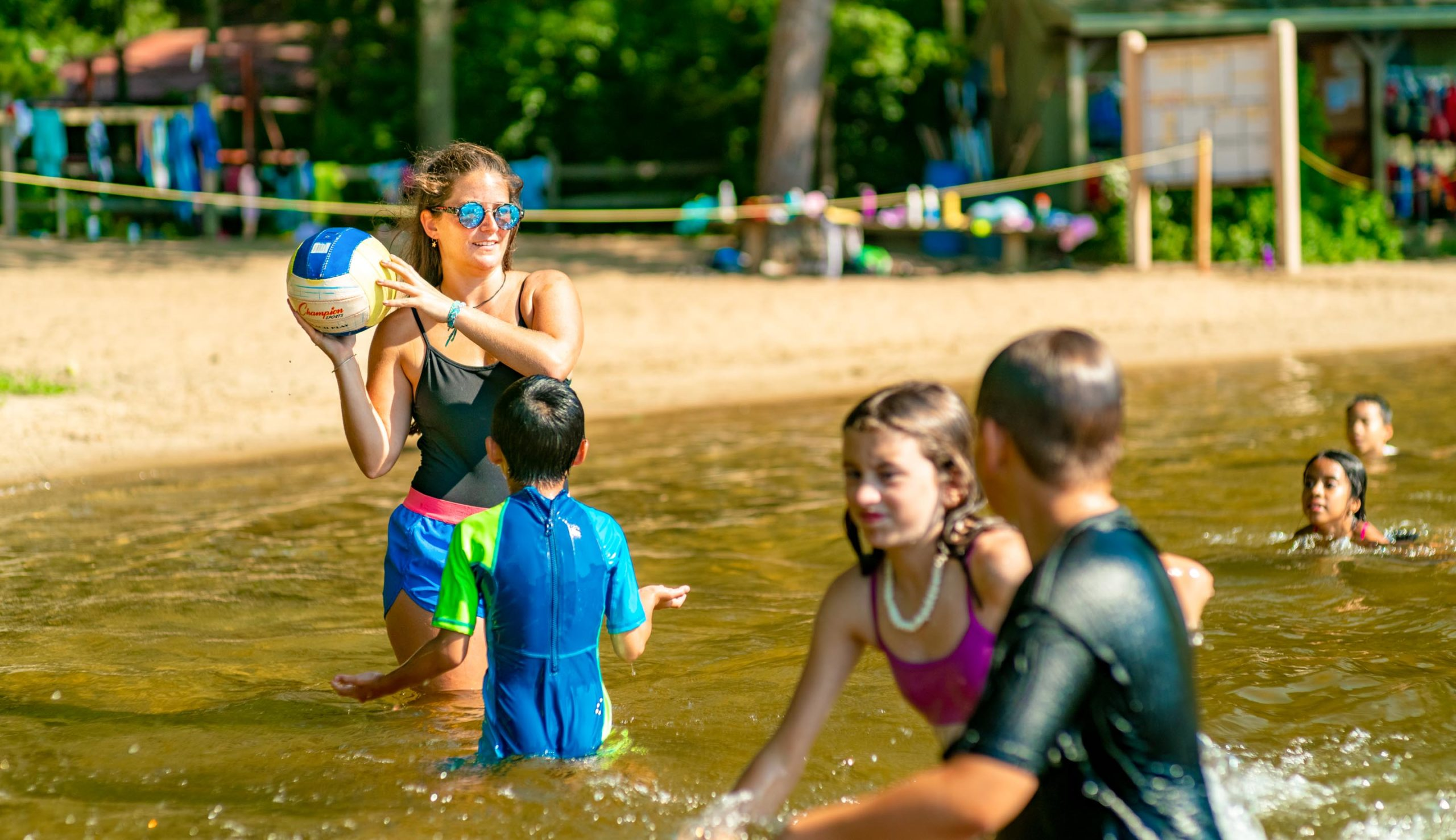 Counselor playing ball with campers in the water
