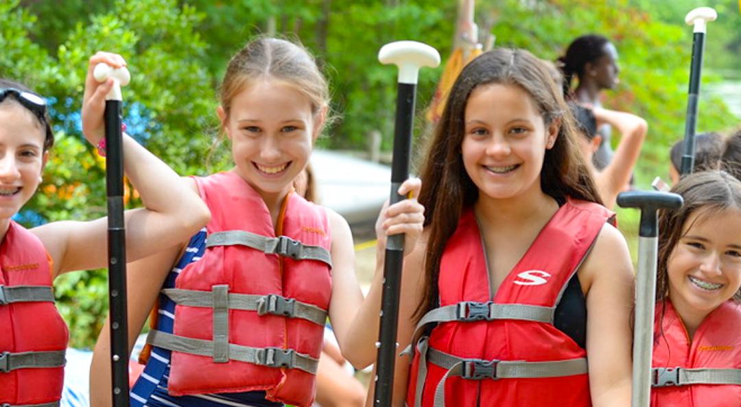 Girls holding kayak paddles