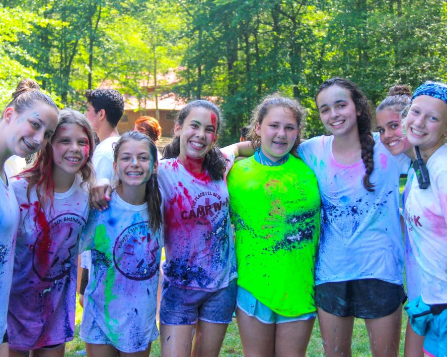 Group of girls standing together with paint on their shirts