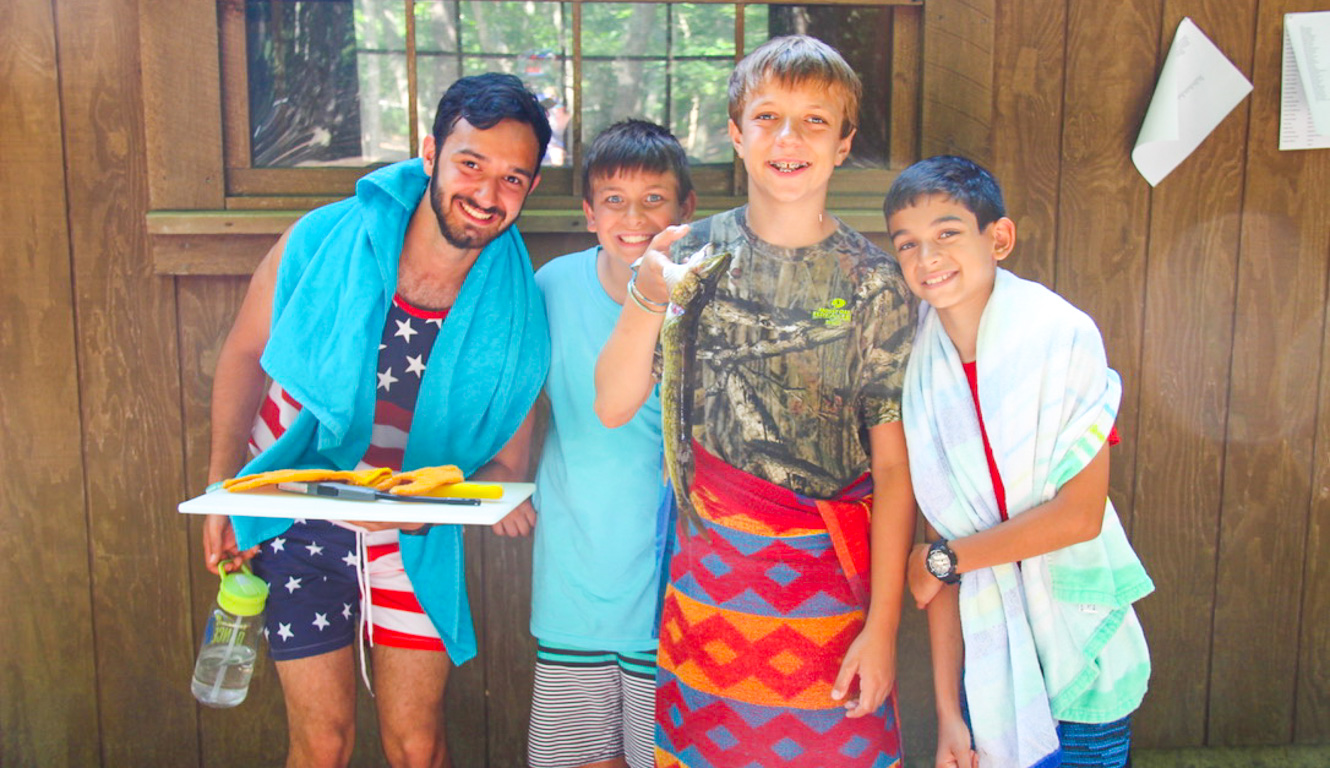 Counselor and campers wrapped in towels after swimming