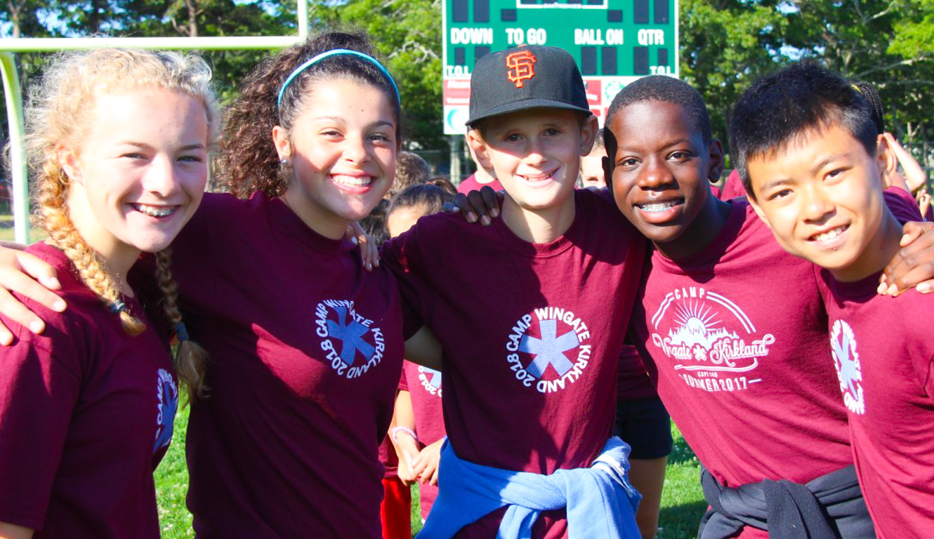 Track meet group smiling together with arms around another